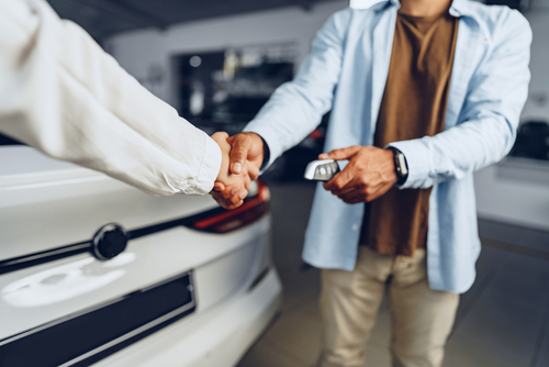 two people handshake inside new car dealership