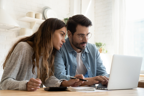 man and woman looking intently at computer screen