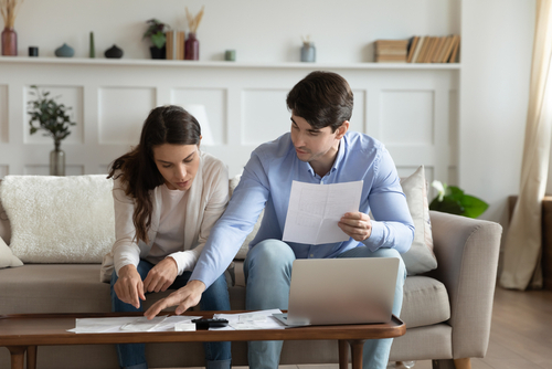 man and woman sitting on couch and looking over paperwork in front of computer screen