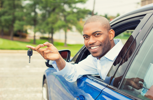 man leaning out of window of car holding keys smiling