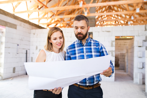 man and woman looking at construction plans