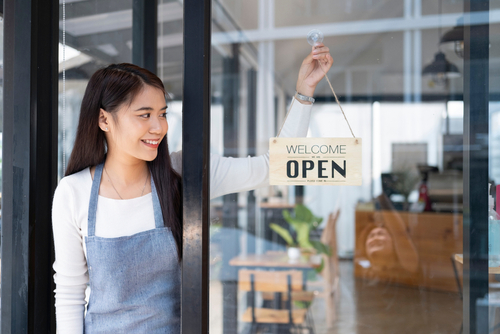 woman putting up now open sign at business