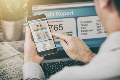 person looking at phone with laptop open in the background with credit score