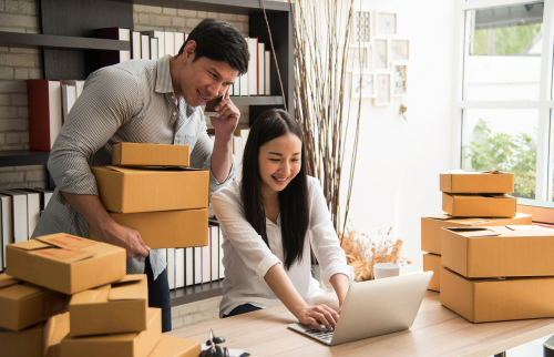 man and woman looking at computer screen with boxes all over the room