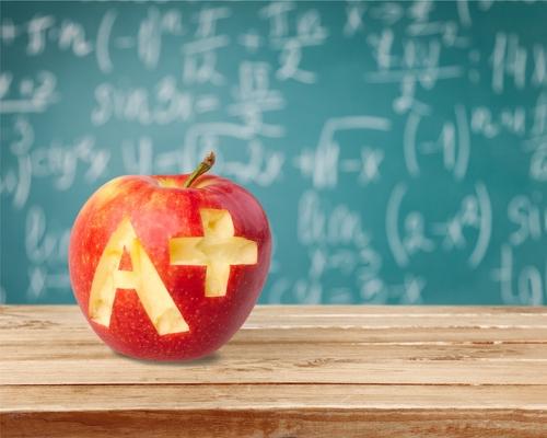 apple on desk in front of chalk board