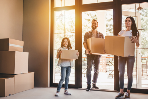 family holding boxes and entering new home