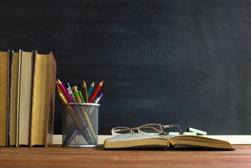 books pencils and glasses on a desk in front of a chalk board