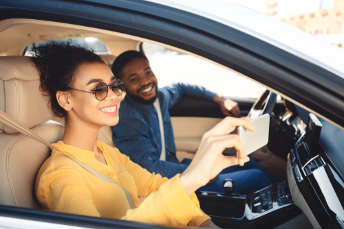 man and woman inside car taking picture with phone