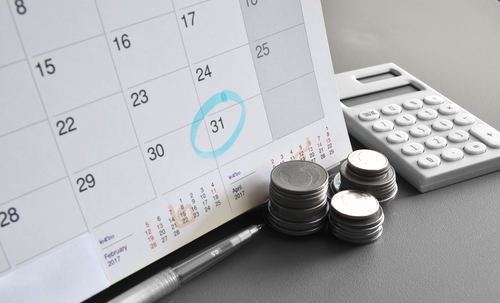 calendar and calculator next to a stack of money