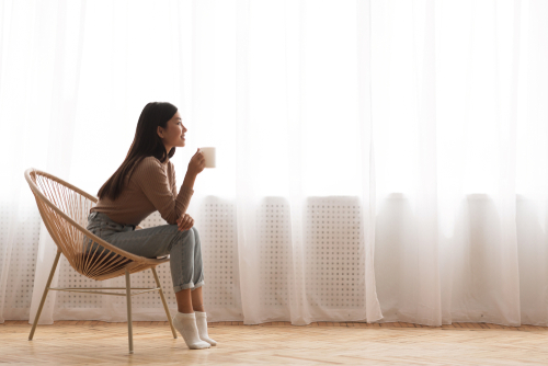 woman sitting in chair drinking coffee