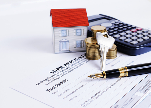 home loan application paperwork and calculator and keys