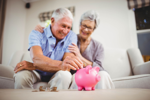 older couple sitting on the couch and putting coins into a pink piggy bank