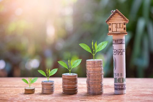 stacks of coins lined up with a small toy house on the highest stack to symbolize increasing your home value
