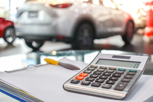 calculator on a desk inside a car dealership